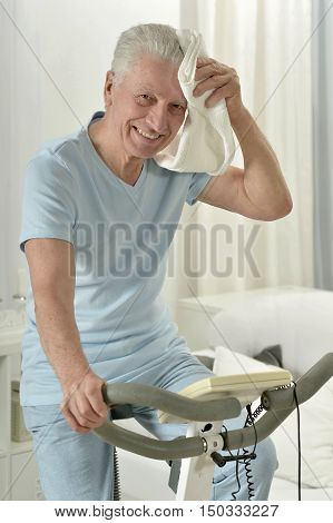 active senior man with bike in gym