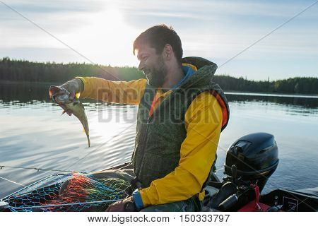 Handsome fisherman catched a haddock in the sea