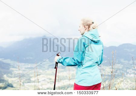 Woman with ponytail wearing outdoor clothing (hardshell waterproof jacket and softshell pants), standing with trekking poles in hands during hiking track in Bavarian Alps - healthy lifestyle concept
