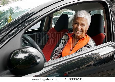happy smiling mature woman driver in her small compact car