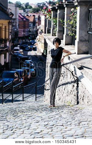 Pretty girl young beautiful woman with short brunette hair in casual wear outdoors on sunny summer day on streetscape