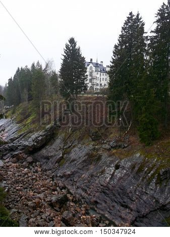 high building with towers on a rocky river bank