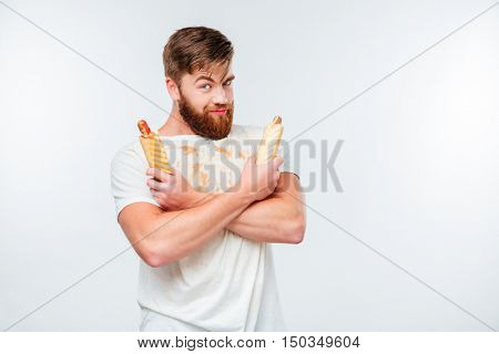 Happy bearded man in filthy shirt holding two hotdogs isolated on white background