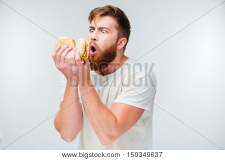 Excited bearded man enjoying eating hamburgers isolated on white background