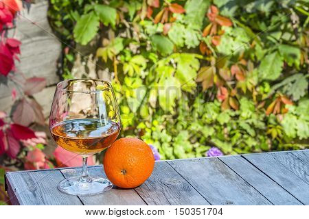 Snifter of brandy with orange on the old table in autumn garden