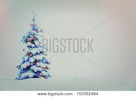 Beautiful decorated christmas tree with snow in a winter snowy landscape.