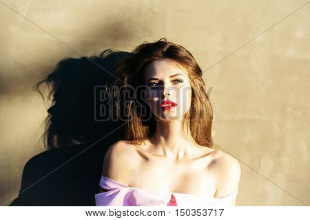 young sexy fashionable woman or girl with long brunette hair and red lips on pretty face with bare shoulders sunny day outdoor near wall