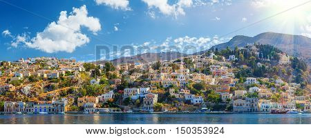 Panoramic shot of the Harbour at Symi Greece with a traditional fishing boat in the foreground. Greece Europe.