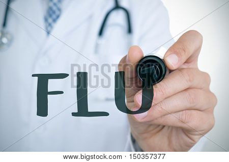 closeup of a young caucasian doctor man writing the word flu in the foreground with a black marker pen