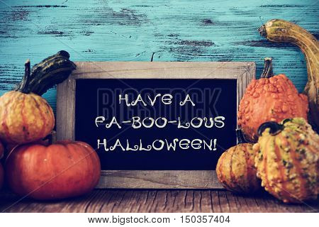 a pile of different pumpkins and a chalkboard with the text have a fa-boo-lous halloween on a rustic wooden surface, against a blue wooden background