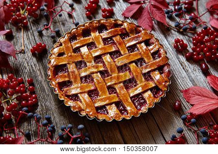 Thanksgiving Traditional raspberry pie tart cake sweet baked pastry food on rustic wooden table background. Autumn mood creative composition decoration.