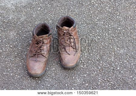 Old brown leather shoes on the floor. Pair of old dirty brown leather shoes.