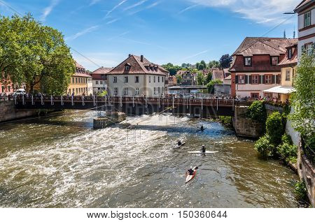 Bamberg Germany - May 22 2016: Tourists on a bridge and canoe slalom on the River Regnitz Bamberg Bavaria Germany Europe. The historic city center is a listed UNESCO world heritage site.