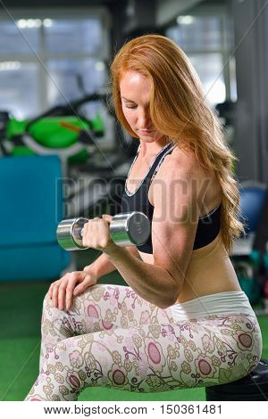 Fitness, sport, exercising lifestyle - Attractive young woman doing weight lifting exercises on biceps at gym.