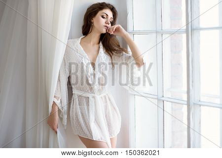 Beautiful Sexy Lady In Elegant White Robe. Close Up Fashion Portrait Of Model Indoors. Beauty Brunet