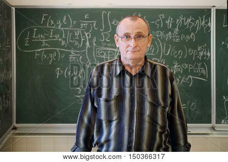 Teacher stands near blackboard with mathematics formulas in school classroom