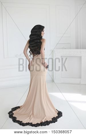 Elegant Lady In Dress. Beautiful Fashion Brunette Woman In Prom Gown With Long Wavy Hair Style Posin