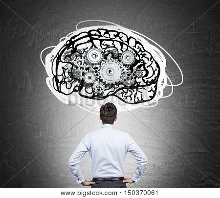 Rear view of man in white shirt standing against blackboard with brain sketch and gears on it. Concept of brain and behaviour studying