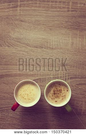 Top view of two cups of coffee late set on the coffee table. Focus on the coffee surface