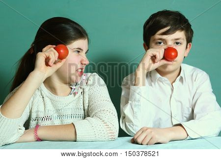siblings with tomato nose close up photo
