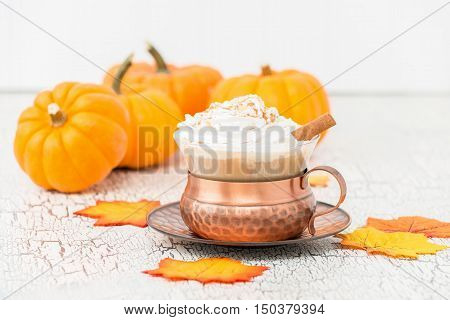 Pumpkin spice latte surrounded by pumpkins and autumn leaves.