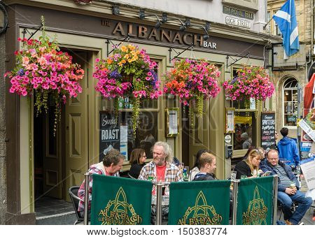 EDINBURGH, SCOTLAND--AUGUST 13, 2016--Some individuals enjoying Sunday lunch at a The Albanach pub on the Royal Mile also are watching street performers of the Fringe festival.