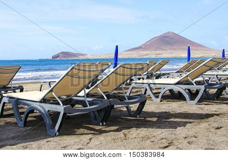 Two sunbeds on a beautiful beach de MedanoTenerife Canary Islands. Concept for vacations or tourism