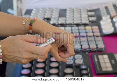 Woman trying lipstick on her hand in the shop.