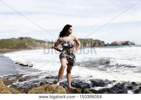Hispanic Woman Standing Arms Akimbo On Rocks At Beach With Waves Cloudy Sky Sand And Shore