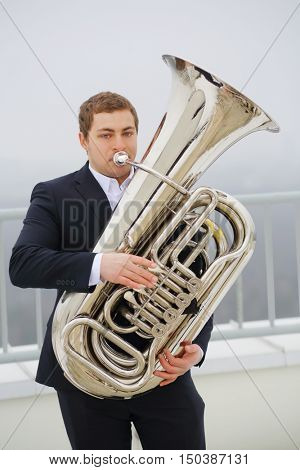 Man in black suit plays tuba on roof of tall building at winter day