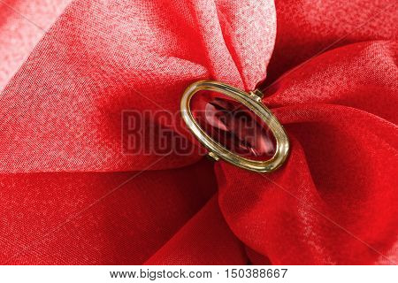 Ruby golden ring on red draped cloth as a background