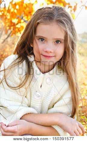 Autumn portrait smiling adorable little girl in the park outdoor