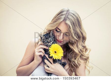 Beautiful girl with a nice flower and cat in hands