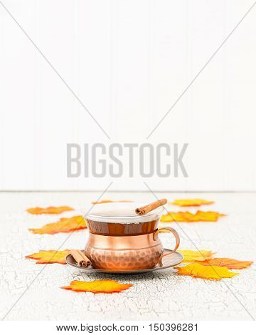 Cup of chai tea with colorful autumn leaves. Plenty of copy space.