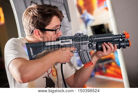Young man playing with a toy shotgun on target in room