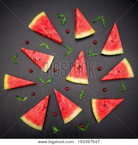 Slices of fresh jucie red watermelon on black background. Decorated with mint and wineberry.