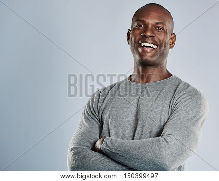 Laughing single handsome young African man with bald head in gray long sleeve shirt and folded arms over neutral background with copy space