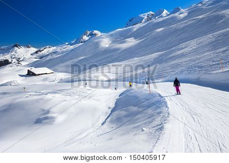 Skiers skiing on the top of the Hoch-Ybrig ski resort in Swiss Alps, Central Switzerland
