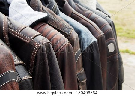 Collection of leather jackets on hangers in the shop. Many new men's leather winter jackets. Background and closeup texture of biker's leather, motorcycle jackets.