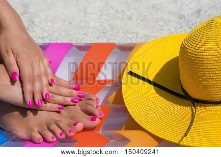 Close-up hand and foot on a pink air mattress in swimming pool. Tropical summer concept.