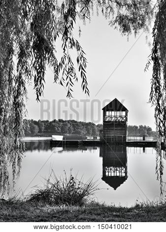 black and white photo of Alum Lake 'Kamencove jezero' in Chomutov city with wooden pier at the end of the summer tourist season