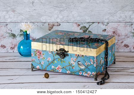 Stunning jewellery chest on a rustic background and decorated with a turquoise vintage paper and gold leaf