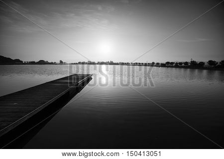 Black and white photography, pier at sunrise in a park of Manresa, Catalonia, Spain. Nice walking area with trees and water pond