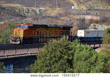 October 4, 2016 in Cajon, CA:  BNSF Freight Train transporting cargo southbound to Los Angeles and beyond taken at a vista point for railroad enthusiasts where people can view trains in the busiest freight train corridor in the nation in Cajon, CA