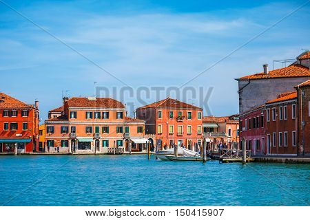 Island Murano in Venice Italy lagoon with dock for boats and coloured old houses antique town at water