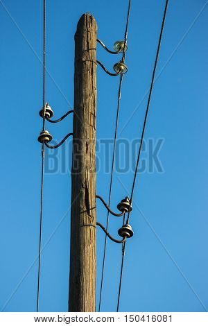 Old wooden pillar with power line against the blue sky