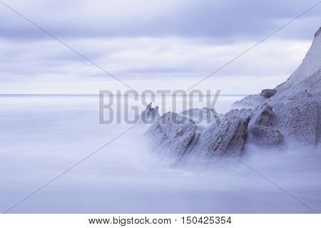 Serene seascape in Atxabiribil beach Biscay Basque Country Spain. Long exposure on a cloudy day.
