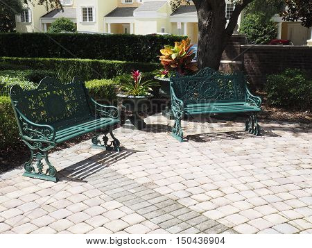 two wrought iron park benches by a patio