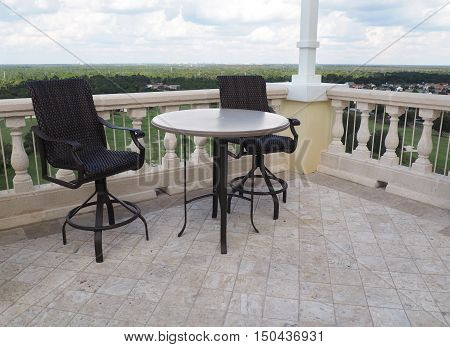two chairs and a table on a rooftop patio
