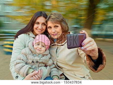 Grandmother with mother and daughter having fun on spinning roundabout. Autumn. Doing selfie. Naturally blur motion